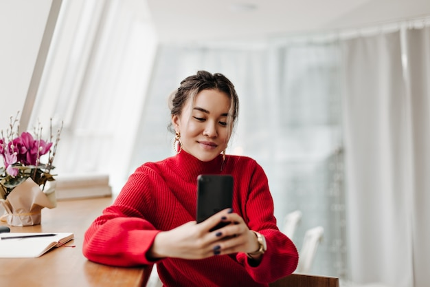Joyful woman in knitted bright sweater makes selfie sitting at table in bright room by window