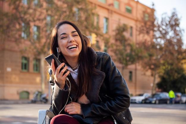 Радостная женщина смеется во время телефонного звонка