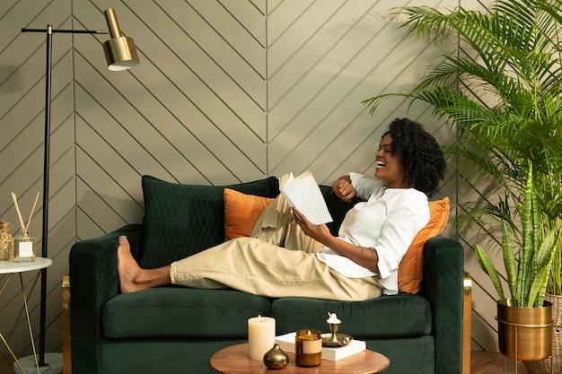 Радостная женщина смеется, читая книгу в гостиной