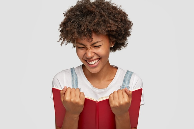 Joyful woman laughs happily while reads funny story from book, shows white teeth, squints face as smiles, dressed in casual outfit, isolated over white wall. people, hobby and reading concept