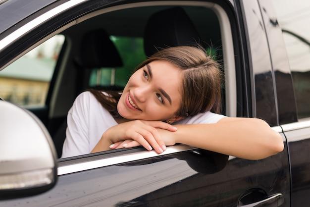 ロードトリップを楽しみながら車の窓にひじをもたれているうれしそうな女性