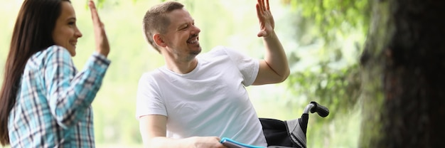 Joyful woman and man in wheelchair holding hands in park in greeting