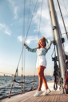 Радостный портрет среднего возраста женщины на палубе парусной яхты, наслаждаясь водным путешествием на летнем прибрежном круизе. женский бизнес-леди на паруснике во время заката. концепция путешествия, приключений, яхтинга и отдыха