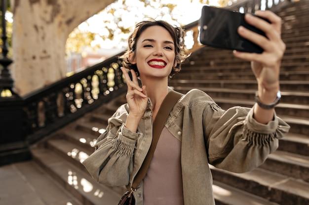 Donna allegra in giacca di jeans verde oliva che mostra il segno di pace e che sorride all'esterno. donna dai capelli corti con labbra rosse che fa selfie sulle scale.