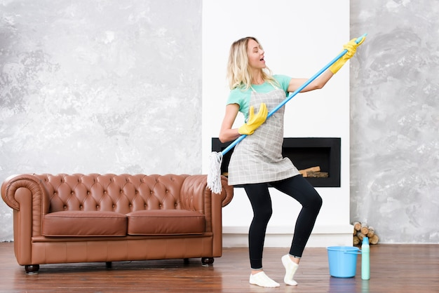 Joyful woman playing mop as guitar standing in house near sofa