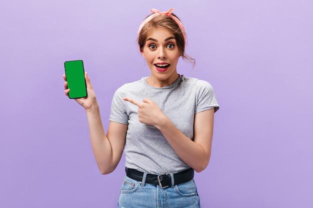 Радостная женщина указывает на телефон на фиолетовом фоне. очаровательная девушка с крутой прической с банданой в летнем наряде смотрит в камеру.