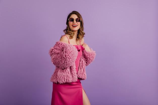 트렌디 한 핑크 드레스를 입고 포즈를 취하는 즐거운 여자