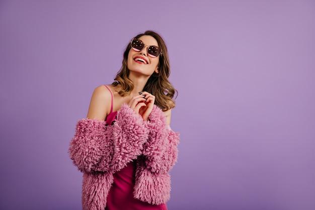 Donna allegra che posa in giacca ecologica viola