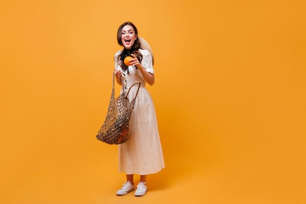 うれしそうな女性がストリングバッグからオレンジを引き出します。オレンジ色の背景にポーズをとる白いミディドレスの女性。