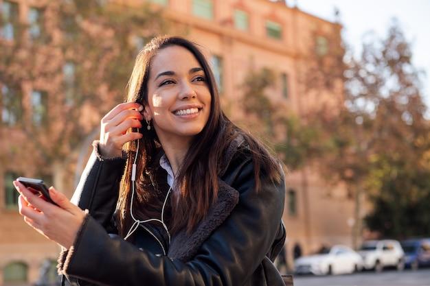 Радостная женщина надевает наушники своего телефона