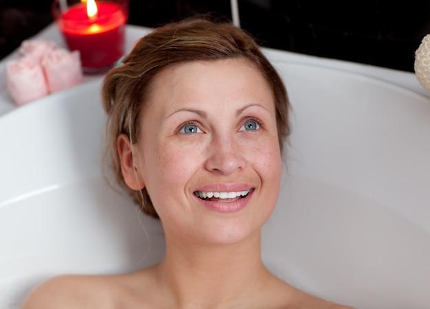 Joyful woman relaxing in a bath