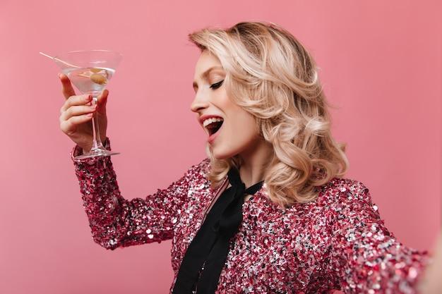 Donna allegra in camicetta lucida posa con bicchiere da martini e prende selfie