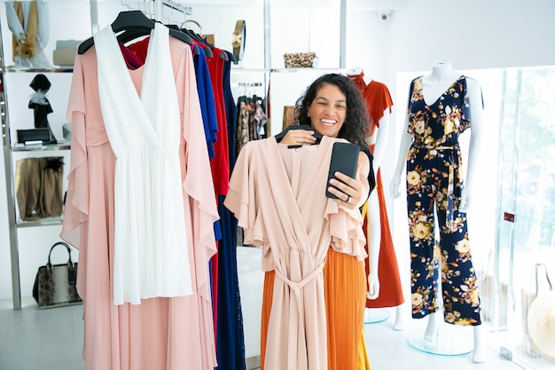 Donna allegra shopping nel negozio di vestiti e amico di consulenza sul cellulare, mostrando il vestito sulla gruccia. cliente boutique o concetto di comunicazione