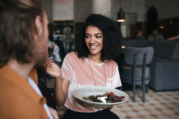 Радостная женщина сидит в ресторане и разговаривает с другом