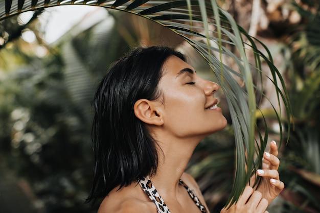 目を閉じてヤシの木を嗅ぐうれしそうな女性。休暇を楽しんでいる美しい日焼けした女性の屋外ショット。