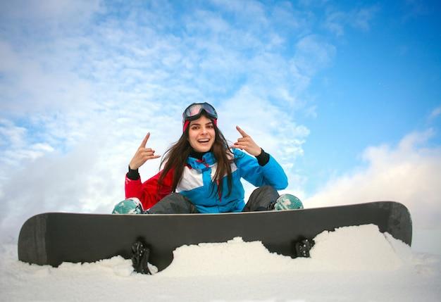 Радостная женщина сноубордист, сидя на вершине горы на голубом небе