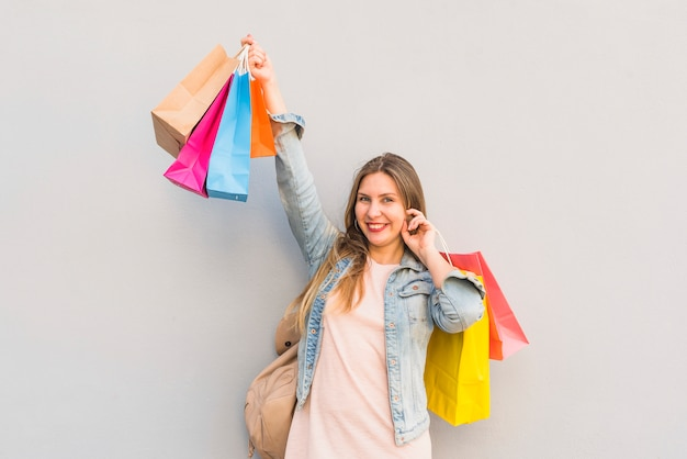 Joyful woman standing with bright shopping bags at light wall