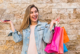 Joyful woman standing with bright shopping bags