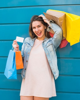Joyful woman standing with shopping bags and credit card