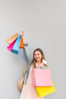 Joyful woman standing with shopping bags and credit card at light wall