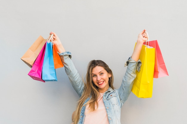Joyful woman standing with shopping bags at light wall