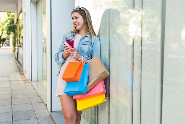Joyful woman standing with shopping bags, smartphone and credit card