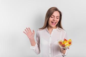 Joyful woman standing with vegetable salad in bowl