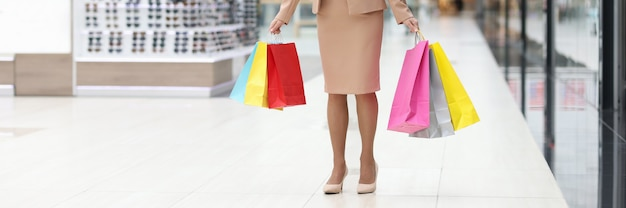 うれしそうな女性は紙の買い物袋を持ってモールに立っています
