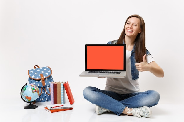 Una studentessa allegra tiene un computer portatile con uno schermo vuoto nero vuoto che mostra il pollice in alto vicino al globo, libri di scuola zaino isolati