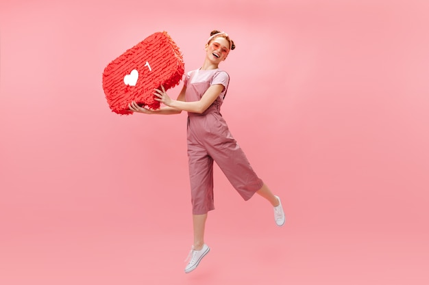 Joyful woman in stylish jumpsuit jumping on pink background, holding like sign.