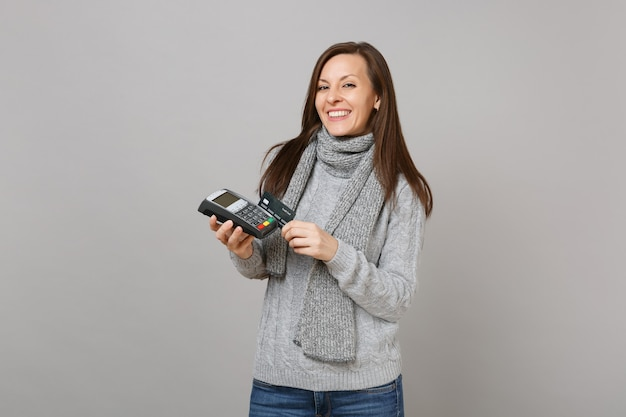 Joyful woman in sweater, scarf hold wireless modern bank payment terminal to process, acquire credit card payments isolated on grey background. lifestyle, people sincere emotions, cold season concept.