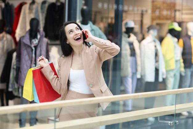 スマートフォンで話し、モールで買い物袋を持っているうれしそうな女性
