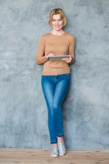 Joyful woman using tablet at wall