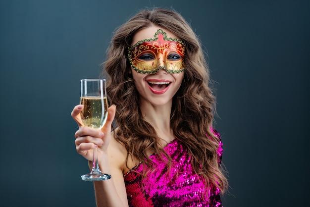 Joyful woman wearing venetian carnival mask smiles broadly against blue background
