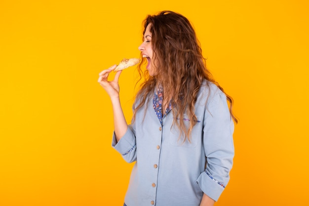 Joyful woman wears fashion pajama going to eat small delicious croissant on yellow wall