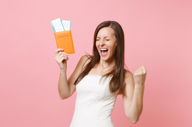 Joyful woman in white dress doing winner gesture, holding passport and boarding pass ticket, going abroad, vacation