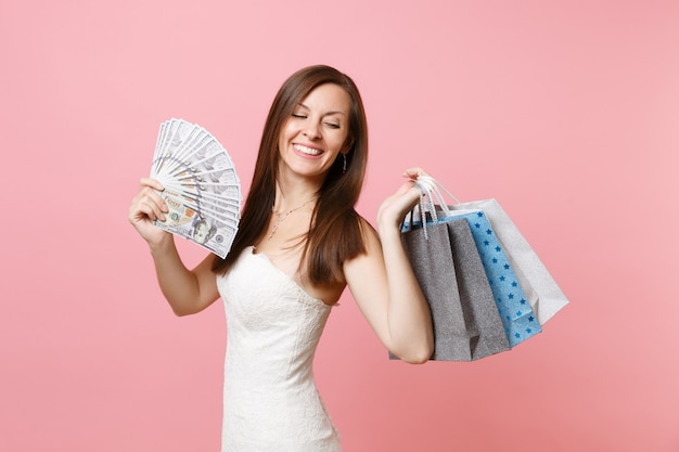 Joyful woman in white dress hold bundle lots of dollars, cash money, multi colored packages bags with purchases after shopping