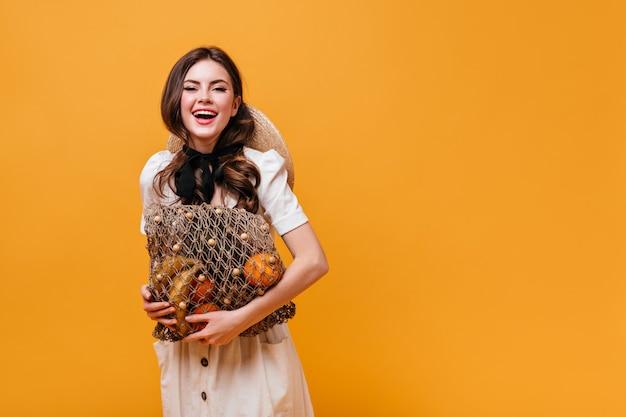 Donna allegra in abito bianco con fiocco nero tiene borsa stringa con frutti su sfondo arancione.