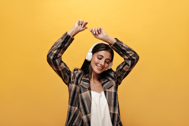 Joyful woman in white top, stylish brown jacket smiles and dances on yellow wall