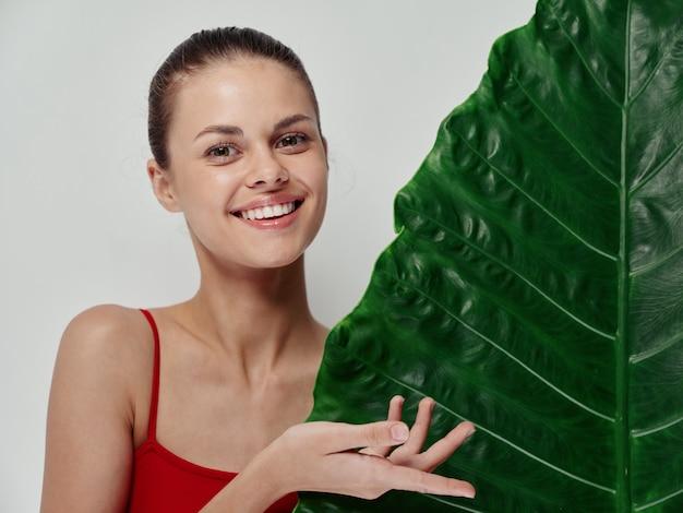 밝은 배경에 남자들의 녹색 잎을 가진 즐거운 여자가 손으로 자른 보기로 몸짓