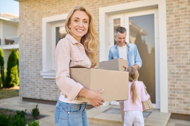 Joyful woman with box and husband with daughter