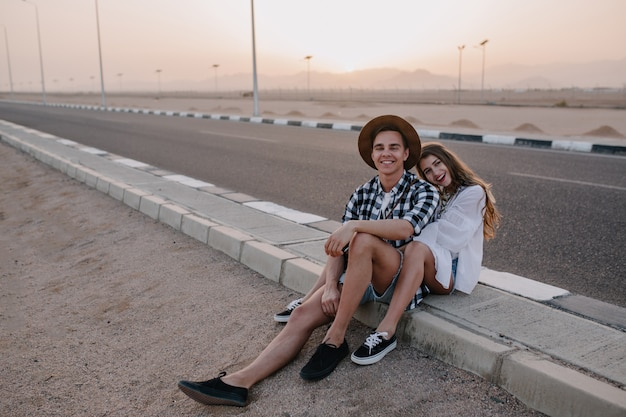 Joyful woman with cute hairstyle sitting on the road, huddled against her boyfriend in trendy hat and laughing. charming young woman and man resting near the highway after travel and enjoys sunset.