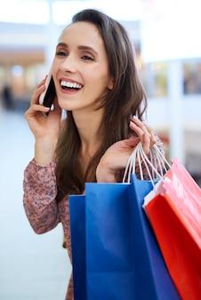 휴대 전화로 이야기 전체 쇼핑 가방을 가진 즐거운 여자