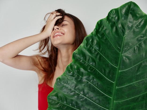 手でトリミングされたビューで頭の上の髪に触れる緑のヤシの葉を持つうれしそうな女性