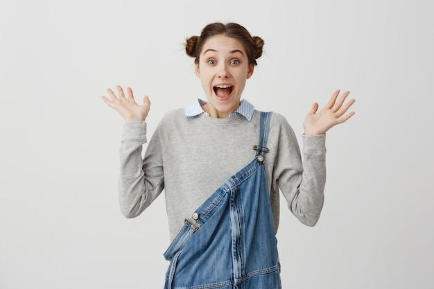 Радостная женщина с прической, стоя с руки вверх, выражая удивление. смешная девчонка жестами кричать в радость и глаза полны счастья. выражения лица