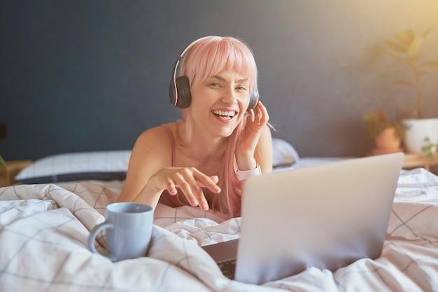 ヘッドフォンでうれしそうな女性はベッドの上のラップトップで音楽を聴きます