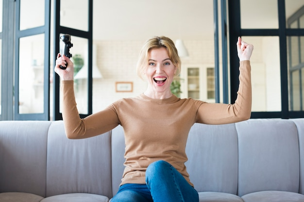 Joyful woman with joystick on couch