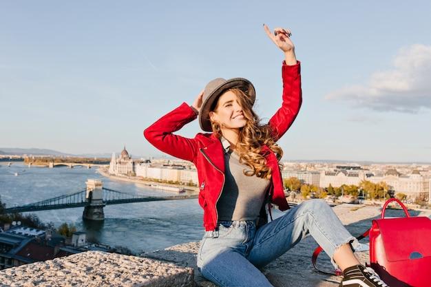 街の背景にポーズをとっている間、明るい茶色の髪の幸せな手を振ってうれしそうな女性