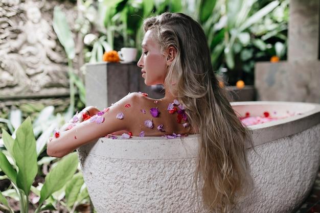 Donna allegra con acconciatura lunga rilassante nella vasca da bagno. bella signora che fa spa con rose nel fine settimana.