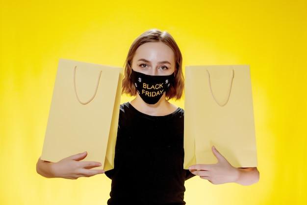 노란색 배경, 쇼핑 여행에 패키지와 함께 즐거운 여자. 스튜디오 초상화입니다. 블랙프라이데이 세일.